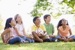 Five young friends sitting outdoors with soccer ball looking up - stock photo