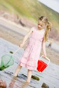 Young girl at beach with net and pail - stock photo