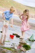 Brother and sister at beach with nets and pail - stock photo
