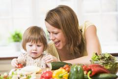 Mother and daughter in kitchen making a salad smiling - stock photo