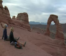 Two ladies sit on rock at delicate arch drinking water Stock Footage