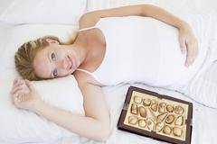 Pregnant woman lying in bed with chocolates smiling Stock Photos