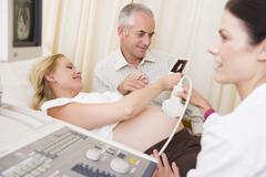 Pregnant woman getting ultrasound from doctor with husband looking at picture - stock photo