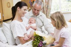 New mother with baby and family in hospital smiling Stock Photos