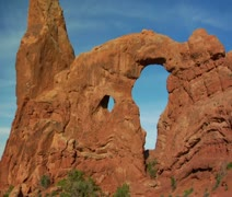 Two female hikers on Turret Arch tilt down Stock Footage