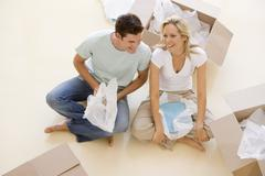 Couple sitting on floor by open boxes in new home smiling Stock Photos