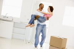 Husband holding wife in new home smiling Stock Photos