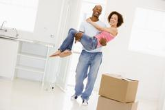 Husband holding wife in new home smiling - stock photo