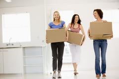Three girl friends moving into new home smiling Stock Photos