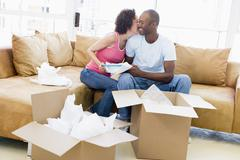 Couple unpacking boxes in new home kissing and smiling Stock Photos