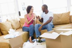Couple toasting champagne by boxes in new home smiling - stock photo