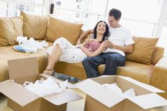 Couple relaxing with champagne by boxes in new home smiling - stock photo
