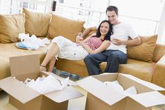 Couple relaxing with champagne by boxes in new home smiling Stock Photos