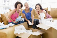 Three girl friends unpacking boxes in new home smiling - stock photo