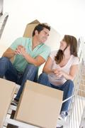Couple sitting on staircase with boxes in new home smiling Stock Photos