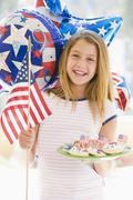 Young girl outdoors on fourth of July with flag and cookies smiling - stock photo