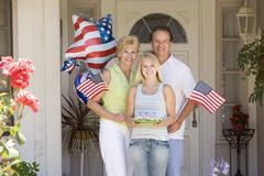 Family at front door on fourth of July with flags and cookies smiling - stock photo
