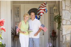 Couple at front door on fourth of July with flags and cookies smiling - stock photo