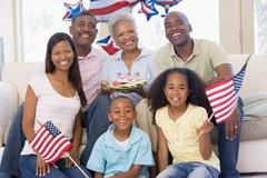Family in living room on fourth of July with flags and cookies smiling - stock photo