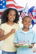 Brother and sister on fourth of July with flag and cookies smiling - stock photo