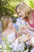 Mother and daughter on Easter looking for eggs outdoors smiling Stock Photos