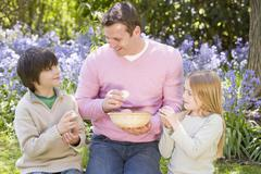 Father and two young children on Easter looking for eggs outdoors smiling - stock photo