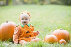 Baby boy outdoors in pumpkin costume with real pumpkins Stock Photos