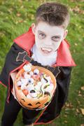 Young boy outdoors wearing vampire costume on Halloween holding candy Stock Photos