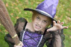 Young girl outdoors in witch costume on Halloween - stock photo
