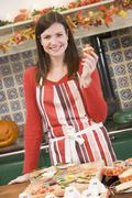 Woman in kitchen making Halloween treats and smiling Stock Photos
