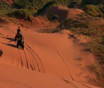 ATV riders on red sand dunes Stock Footage