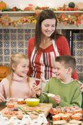 Mother and two children at Halloween making treats and smiling - stock photo