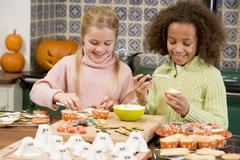 Two young girl friends at Halloween making treats and smiling - stock photo