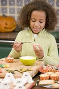 Young girl at Halloween making treats and smiling Stock Photos