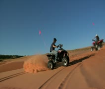 Slow-motion ATV riders kick up sand Stock Footage