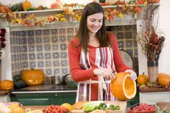 Woman carving jack o lantern on Halloween and smiling - stock photo
