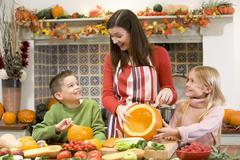 Mother and two children carving jack o lanterns on Halloween and smiling - stock photo