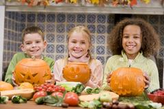 Three young friends on Halloween with jack o lanterns and food smiling - stock photo
