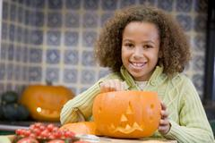 Young girl on Halloween with jack o lantern smiling Stock Photos