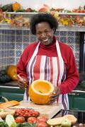 Woman on Halloween making jack o lantern smiling - stock photo