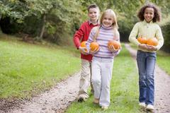Three young friends walking on path with pumpkins smiling Stock Photos
