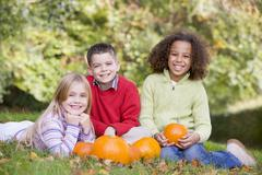 Three young friends sitting on grass with pumpkins smiling - stock photo