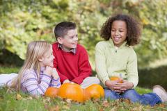 Three young friends sitting on grass with pumpkins smiling Stock Photos