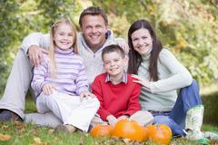 Family sitting on grass with pumpkins smiling - stock photo