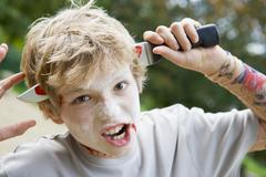 Young boy with scary Halloween make up and plastic knife through head Stock Photos