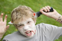Young boy with scary Halloween make up and plastic knife through head - stock photo