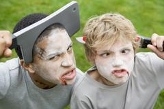 Two young boys with scary Halloween make up and plastic knives through their - stock photo