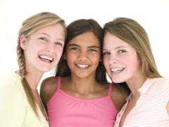 Three girl friends together smiling - stock photo