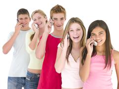 Row of five friends on cellular phones smiling Stock Photos