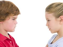 Brother and sister staring at each other - stock photo